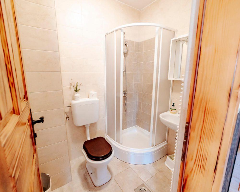 Das kleine Badezimmer der Villa Alma ist mit einer Toilette und einer kleinen Dusche ausgestattet.