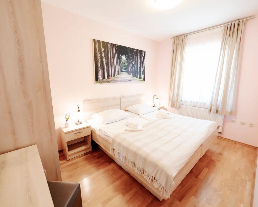 Das große Schlafzimmer verfügt außerdem über ein großes Fenster mit Gardinen, einen Kleiderschrank und einen kleinen Teppich vor dem Doppelbett.