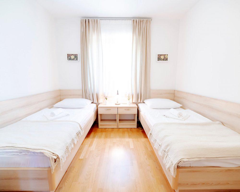 Das Zweibettzimmer besitzt ein großes Fenster mit Gardinen und zwei Nachttische mit Nachtleuchten.