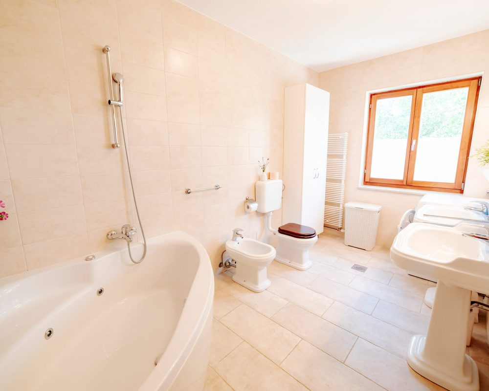 Das große Badezimmer besitzt außerdem ein großes Fenster mit Blick ins Grüne und einen großen Badschrank.