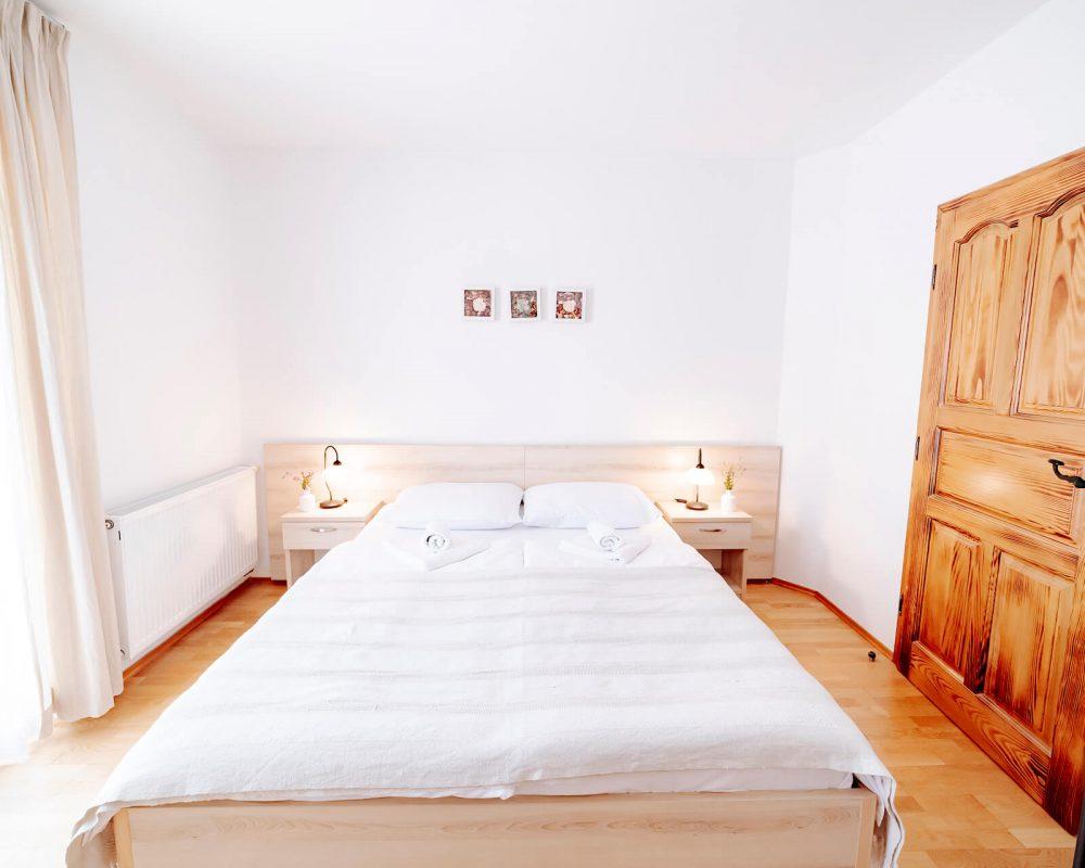 Das Schlafzimmer mit dem Doppelbett der Villa Alma besitzt auch einen eigenen kleinen Balkon als Rückzugsort.