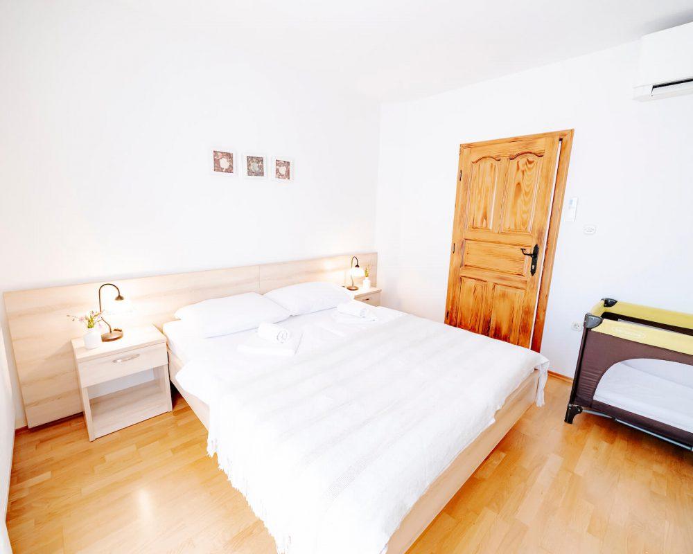 Das gemütliche Schlafzimmer, der Villa Alma, hat ein komfortables Doppelbett mit zwei Nachttischen, zwei Tischlampen sowie ein Babybett..