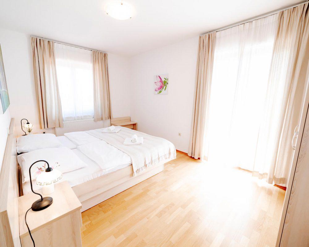 Das Ferienhaus Villa Alma hat ein Schlafzimmer mit einem schicken Doppelbett, zwei Nachttischen und hellen Gardinen.