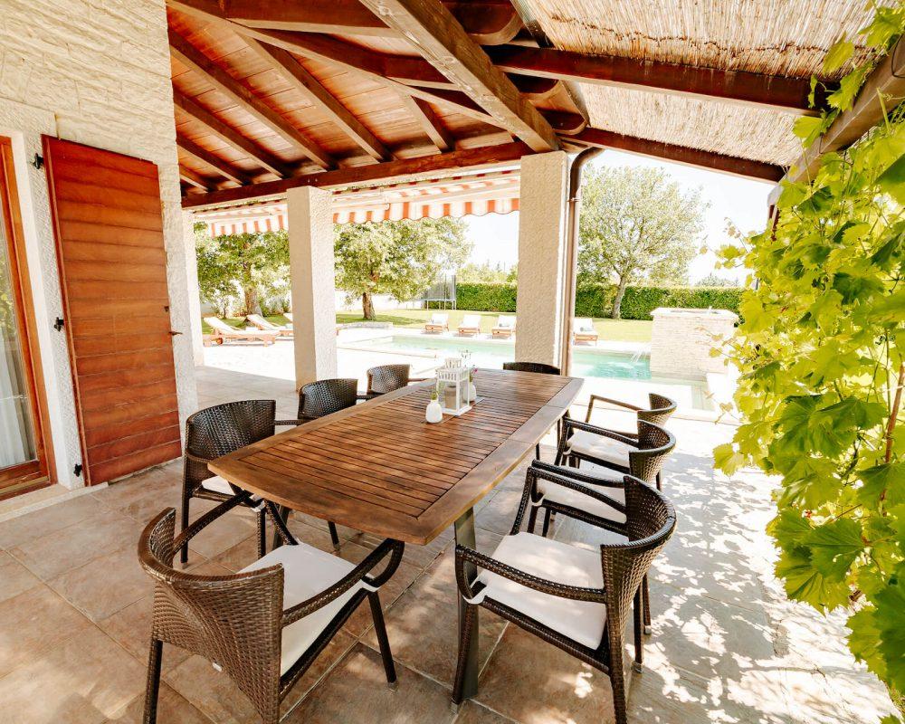 Auf der überdachten Terrasse steht ein langer hübscher Esstisch mit acht Sitzmöglichkeiten. Am Rand der Terrasse wachsen Weinstöcke.