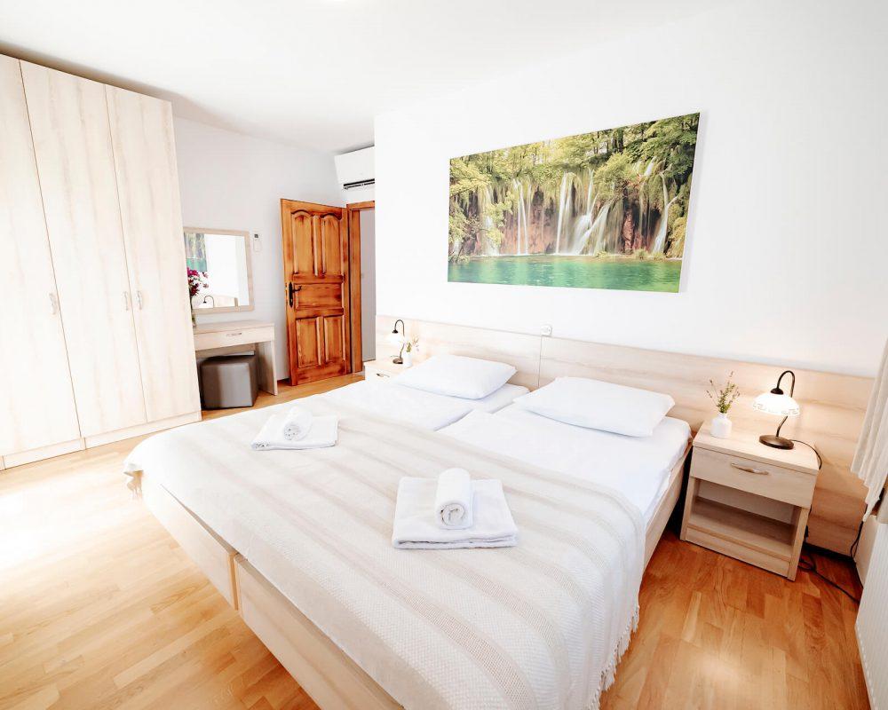 Das gemütliche Schlafzimmer, der Villa Alma, hat ein komfortables Doppelbett mit zwei Nachttischen, zwei Tischlampen und mehr..