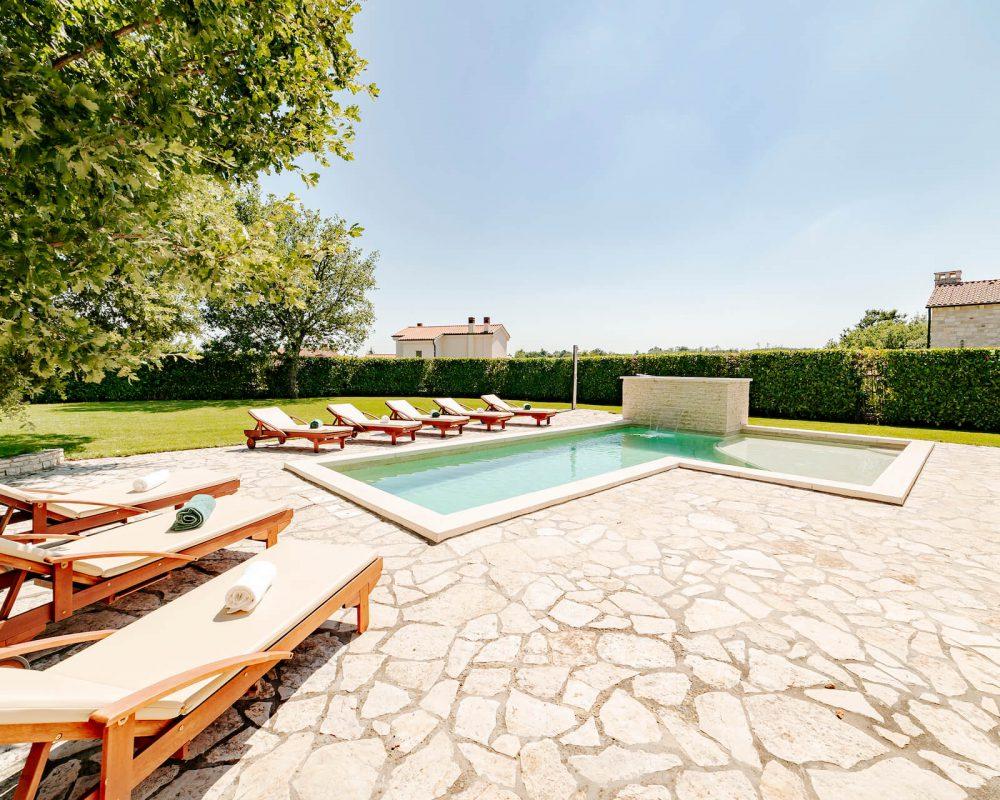 Auf der Terrasse ist ein 30m² großer Swimmingpool mit Acht schicken Sonnenliegen aus Holz.