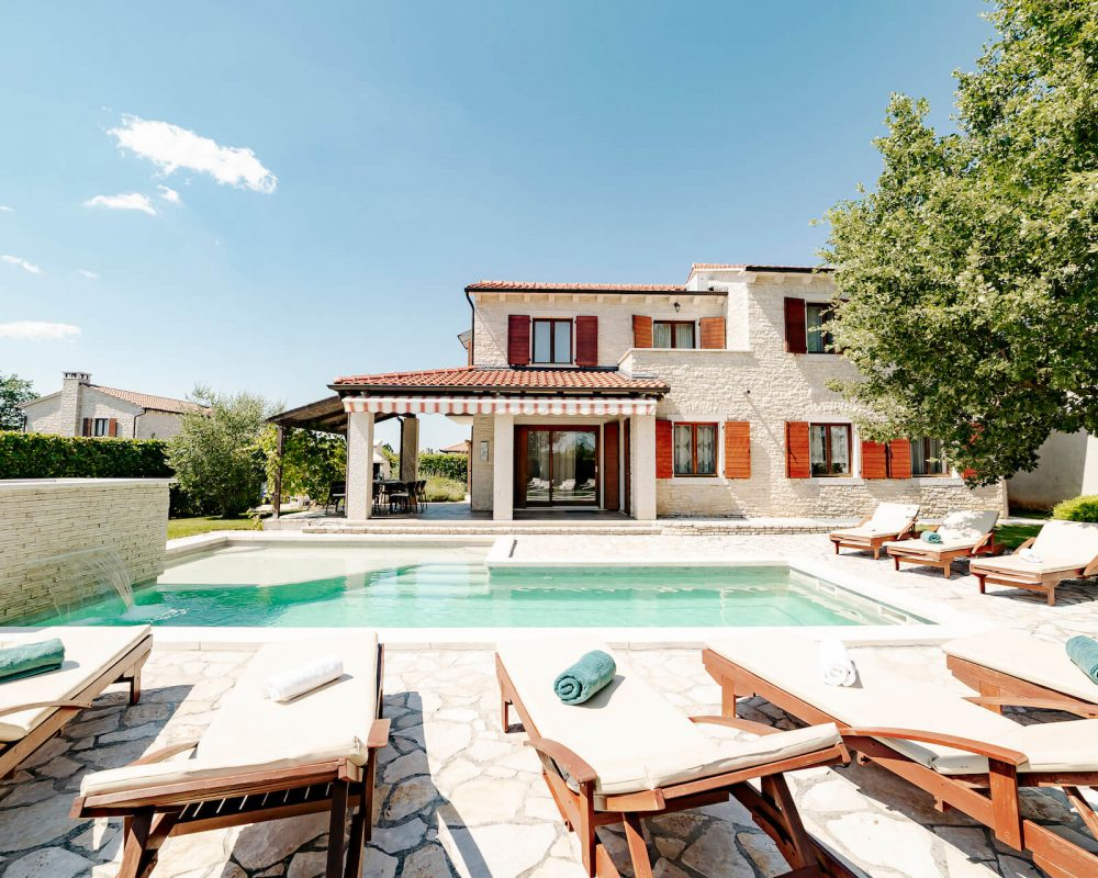 Die Villa verfügt über eine große Steinterasse mit Swimmingpool, Sonnenliegen und einem Sonnenschirm.