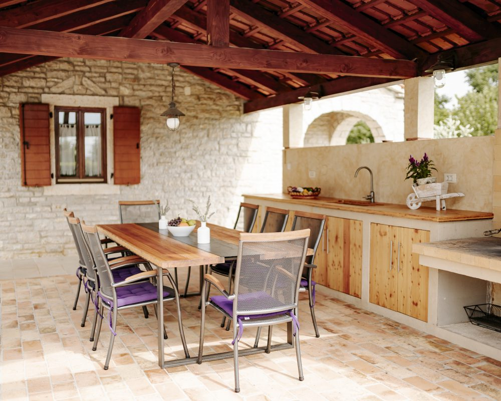 Die schattige Außenküche besitzt einen langen Esstisch mit Acht Stühlen.
