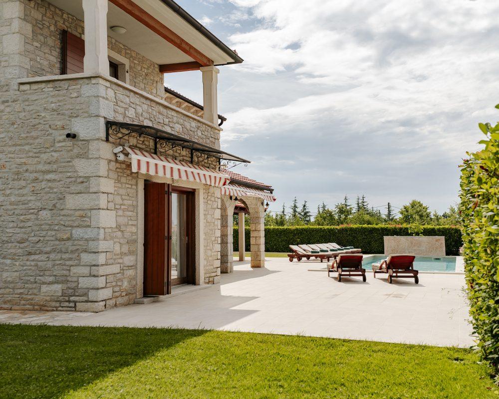Im Außenbereich der Villa befindet sich eine große Terrasse mit bequemen Sonnenliegen.