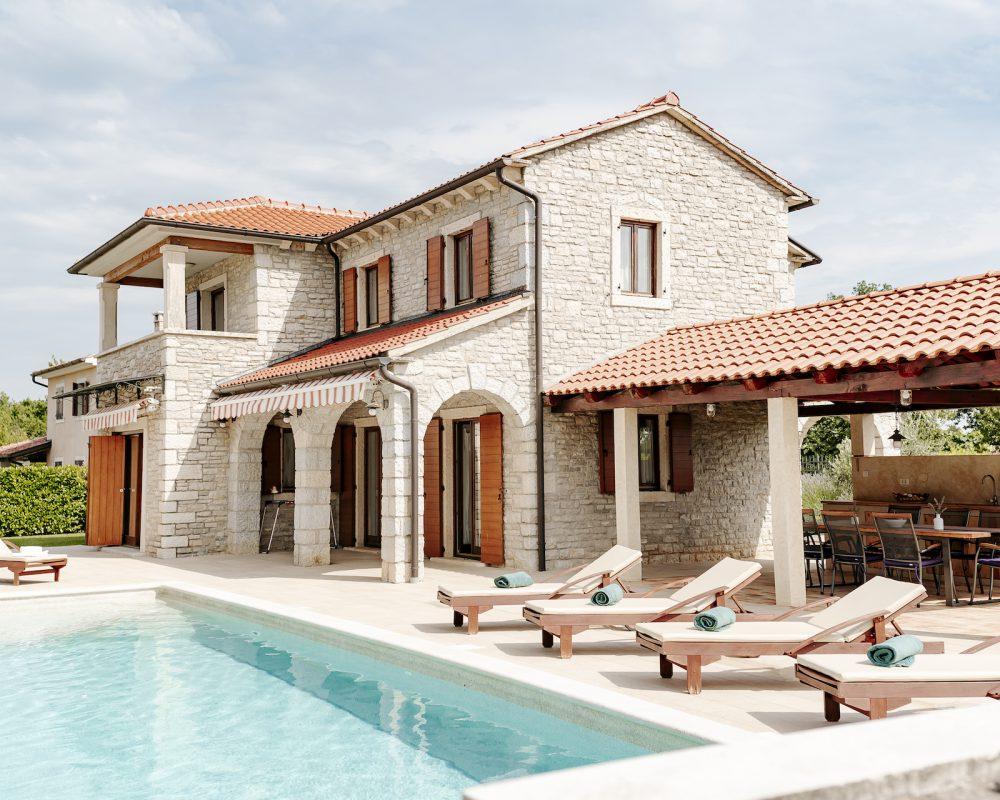 Der erfrischende Swimmingpool der Villa verfügtüber einen kleinen, eleganten Wasserfall. Auf der Terrasse stehen Sonnenliegen um den Pool.