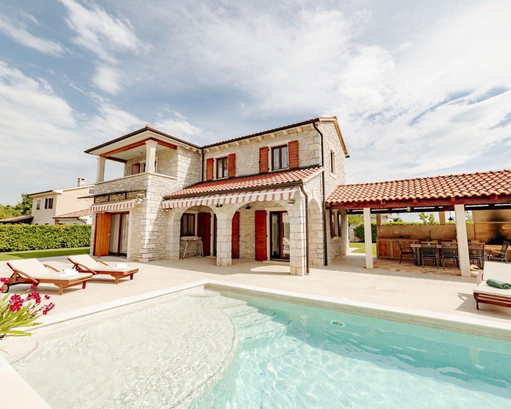 Auf dem Grundstück der Villa Begonia der Villas Istria bringt der große Swimmingpool der ganzen Familie Spaß. Ein großes Trampolin und die rustikale Außenküche sorgen bei Kindern und Eltern für ein entspanntes Urlaubsfeeling.
