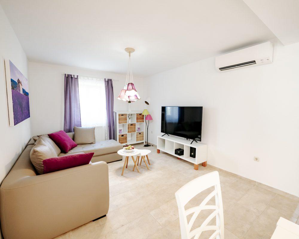 In dem Wohnzimmer befinden sich eine Eckcouch und ein Regal mit einem Flachbild-SAT-TV.
