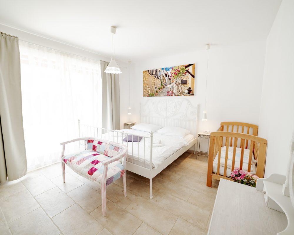 Auf der einen Seite des Doppelbettes ist ein Kinderbett. Auf der anderen Seite befindet sich der direkte Zugang zur großen Terrasse.