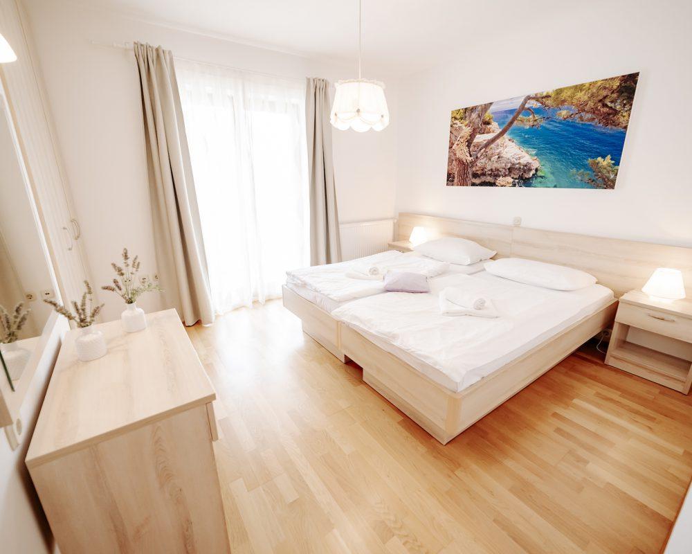 Das große Schlafzimmer besitzt einen kleinen eigenen Balkon und hat ein schönes Bild der kroatischen Natur..