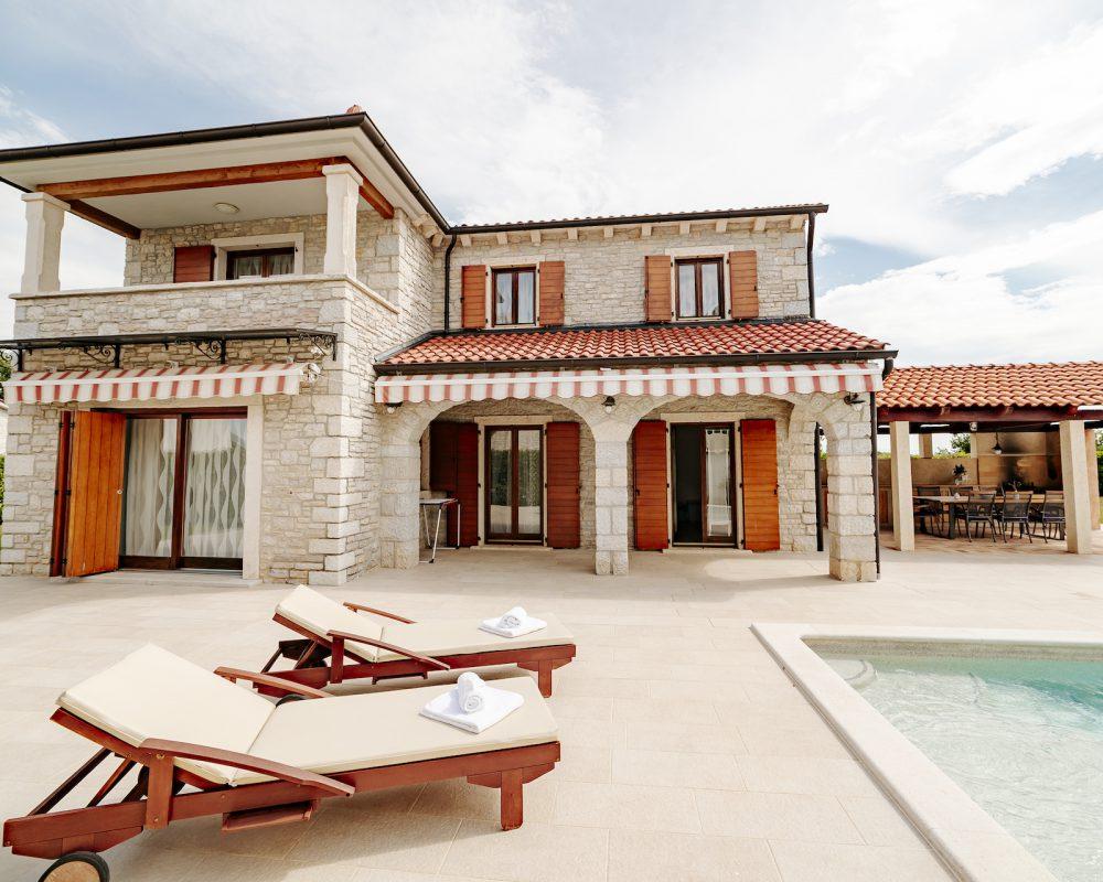 Die Villa Begonia verfügt im Außenbereich über eine Terrasse mit Außenpool und Loungemöbeln, eine gepflegte Grünanlage, ein Trampolin und eine rustikale Außenküche.