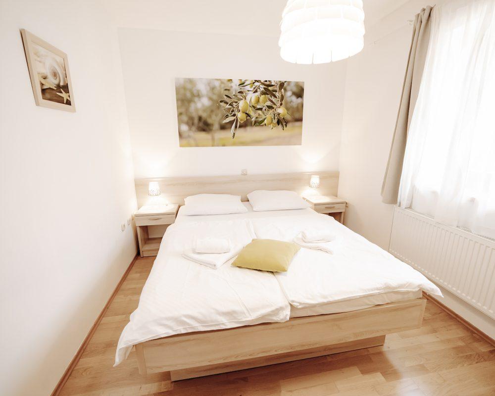 Das Schlafzimmer hat zwei kleine Tische mit einer Schublade. Auf beiden Tischen befinden sich Nachtlampen.