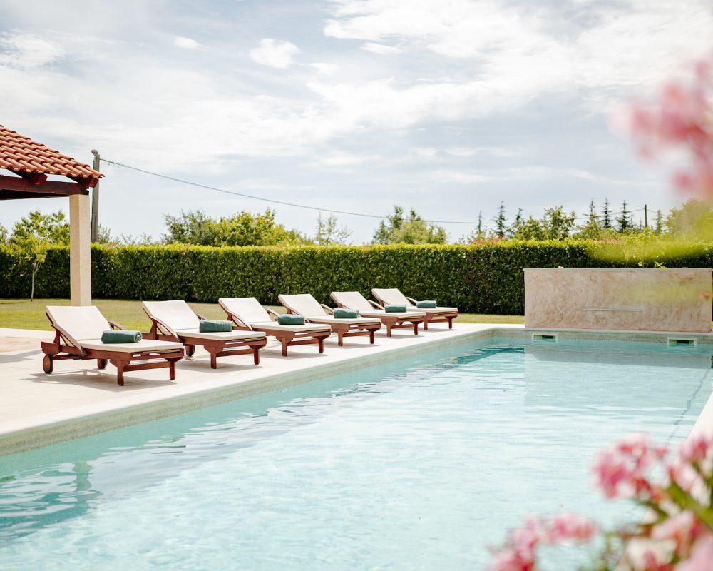 Der 50m² große Pool hat einen flachen Bereich, perfekt für kleine Kinder oder zum sitzen. Ein paar Treppenstufen führen in den tieferen Bereich mit Wasserfall.