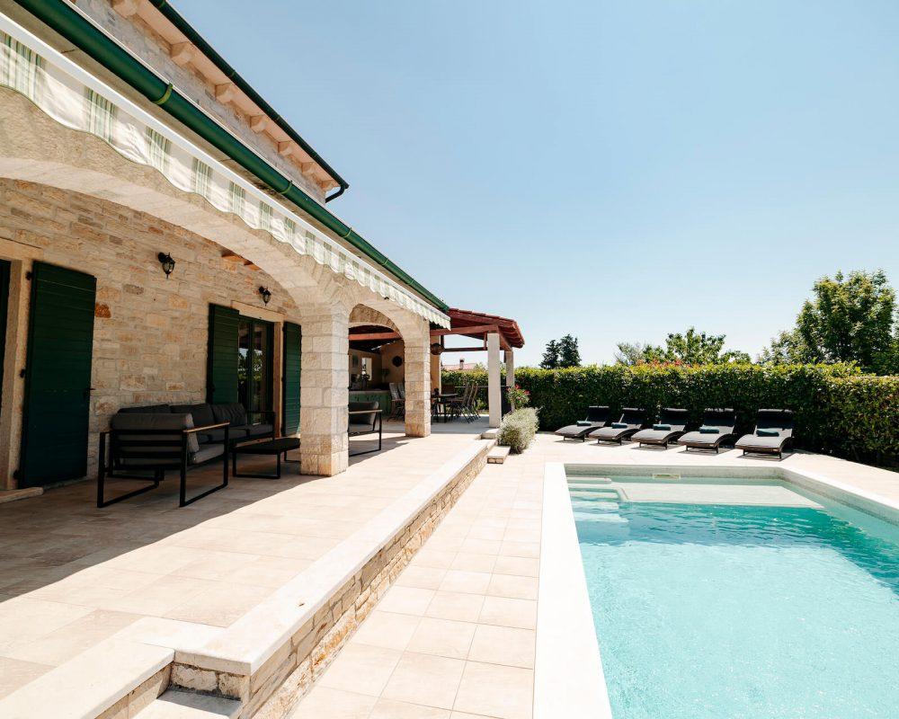 Auf der überdachten Terrasse stehen bequeme Loungemöbel. Von dort aus hat man einen tollen Blick auf den Swimmingpool und die Natur.