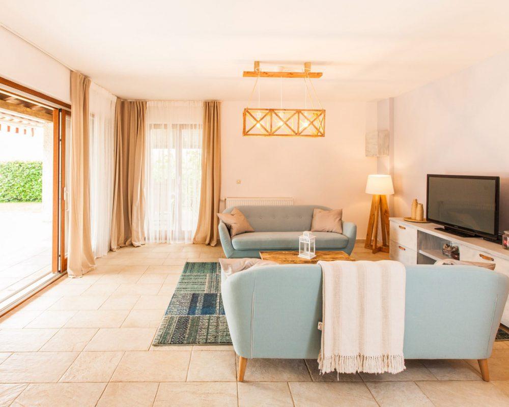 Der große helle Wohnbereich ist mit zwei Couchs, einem Regal mit Flachbildfehrnseher und einem direkten Zugang zum Außenbereich.