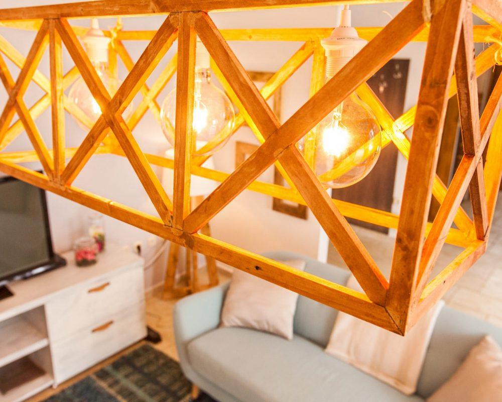 An der Decke des Wohnzimmers ist eine besondere Lampe aus Holz.