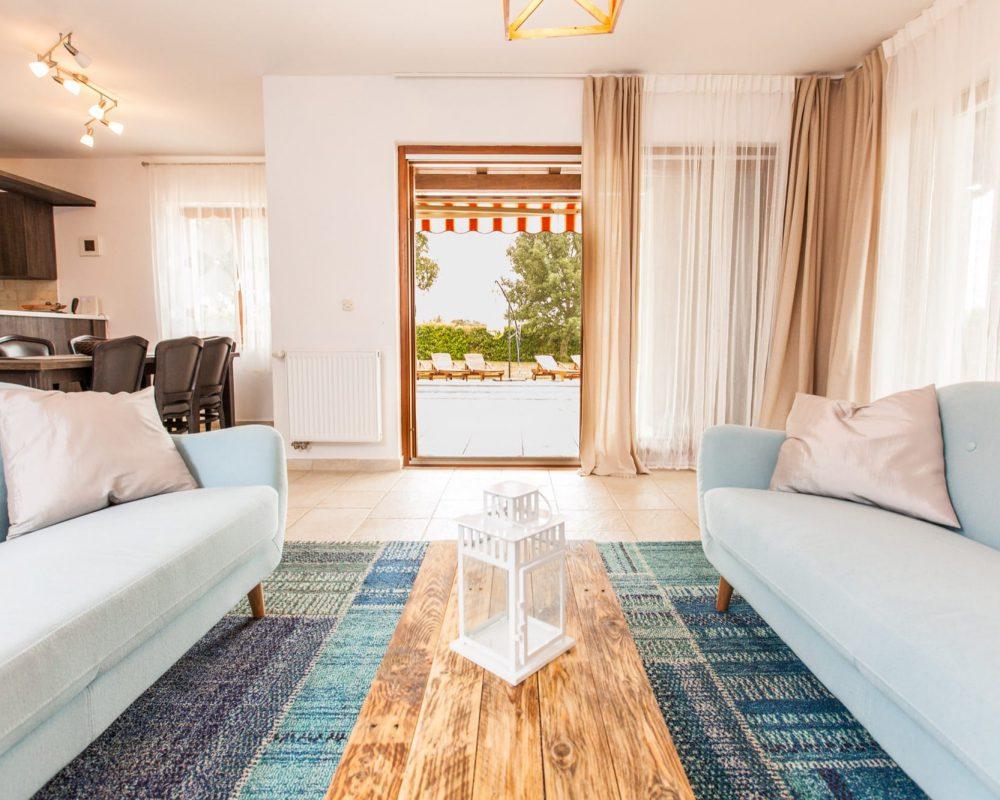 Der Wohnbereich verfügt über zwei sich gegenüberstehende Couchs auf einem großen Teppich. Zwischen den zwei Couchs ist ein schmaler schicker Couchtisch.