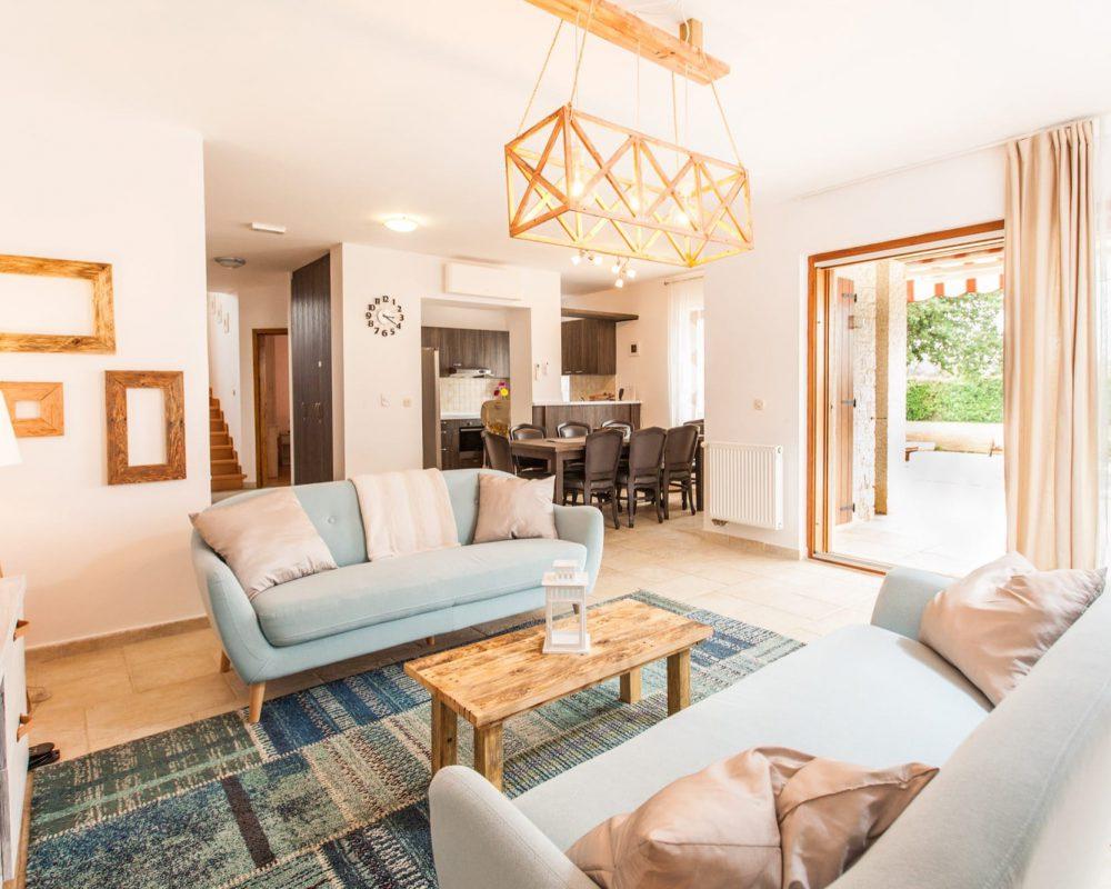 Der Wohnbereich und die Küche mit Essbereich sind direkt miteinander verbunden. Über eine geschwungene Holztreppe kommt man in die obere Etage. Eine Glasschiebetür führt vom Wohnzimmer direkt in den Außenbereich.