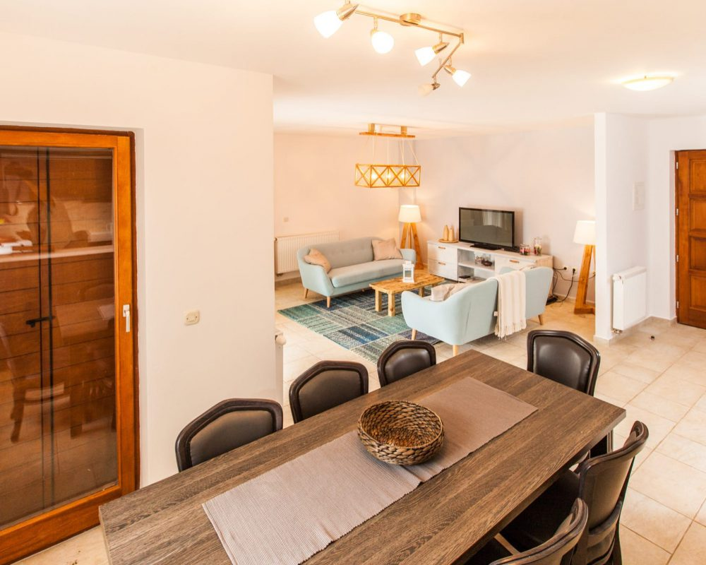 Im Essbereich der Villa Alma befindet sich ein großer schicker Esstisch mit Acht Stühlen. Eine Tür führt direkt zur Terrasse in den Außenbereich.