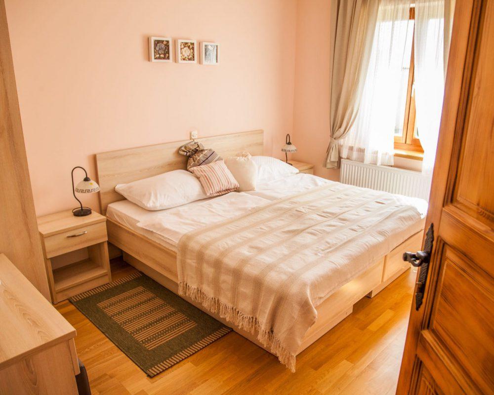Das große Schlafzimmer verfügt außerdem über ein großes Fenster mit Gardienen, einen Kleiderschrank und einen kleinen Teppich vor dem Doppelbett.