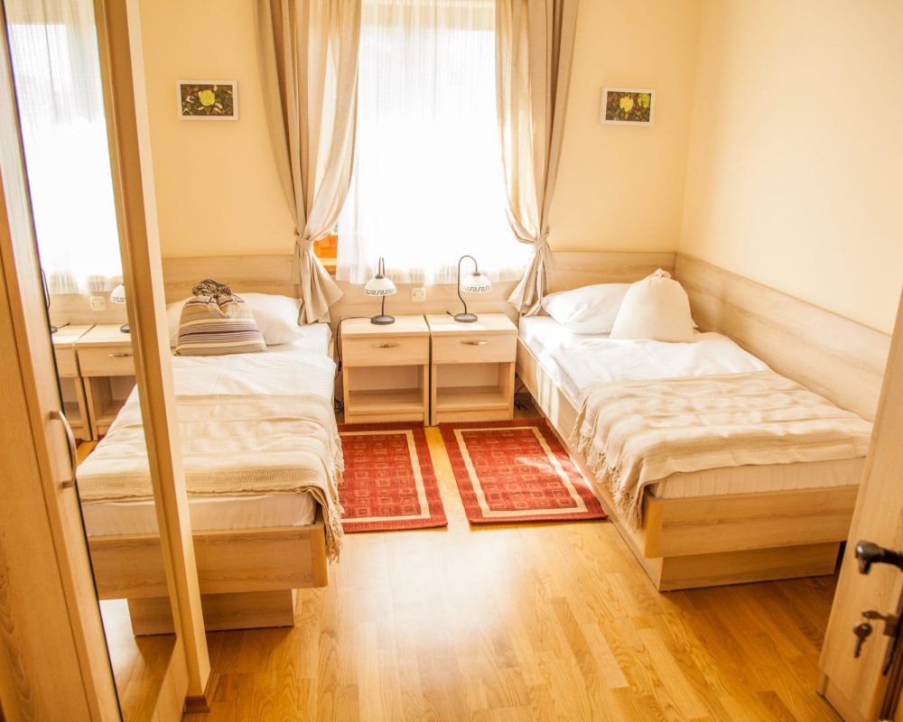 Das Zweibettzimmer verfügt über ein großes Fenster zwischen den zwei komfortablen Einzelbetten. Vor den Betten sind zwei kleine Teppiche.