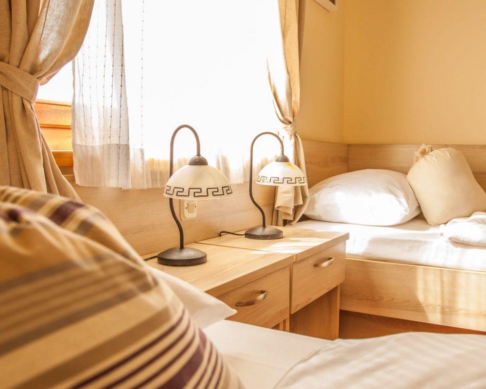 Das Zweibettzimmer besitzt ein großes Fenster mit Gardienen und zwei Nachttische mit Nachtleuchten.