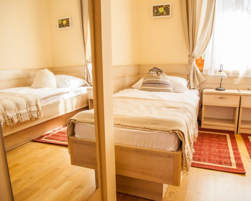 Das Schlafzimmer mit den Einzelbetten hat einen hohen Kleiderschrank und zwei kleine Nachttische mit Tischleuchten.