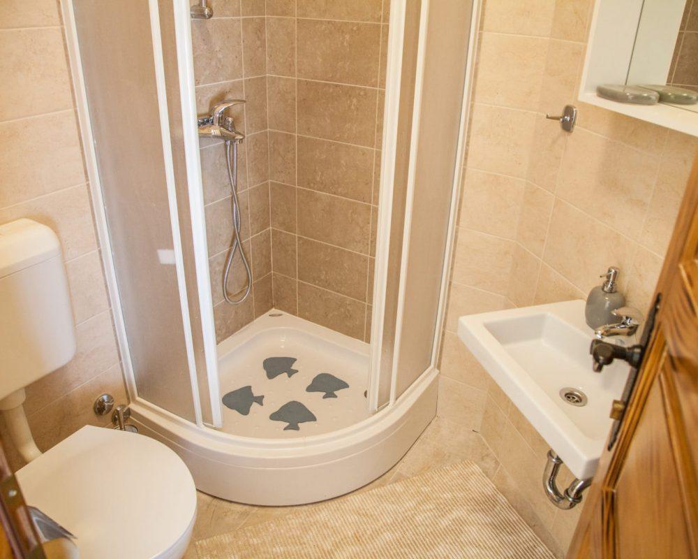 Das kleine Badezimmer der Villa Alma verfügt über eine kleine Dusche, ein Waschbecken und eine Tiolette.
