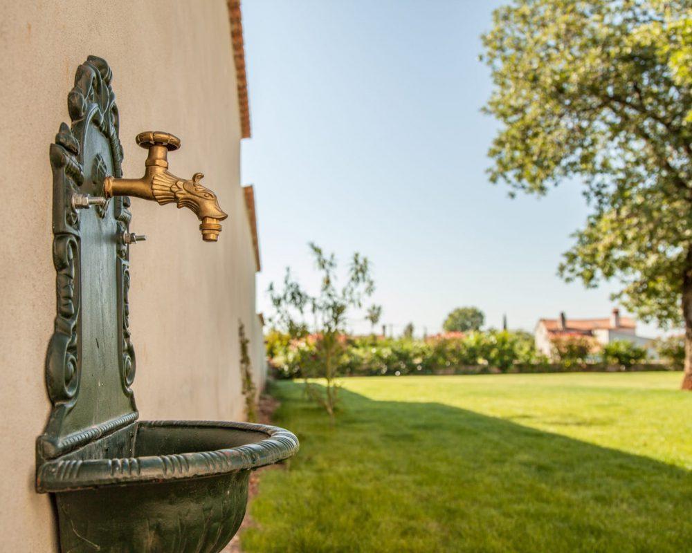 An der Hauswand der Villa Alma ist ein verzierter Wasserhahn mit einem kleinen Becken.