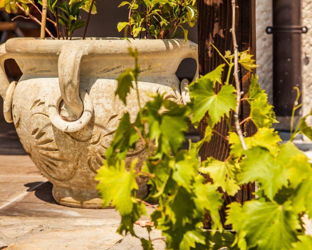 Auf der überdachten Terrasse des Ferienhauses, steht ein verziehrter Blumentopf aus Stein.