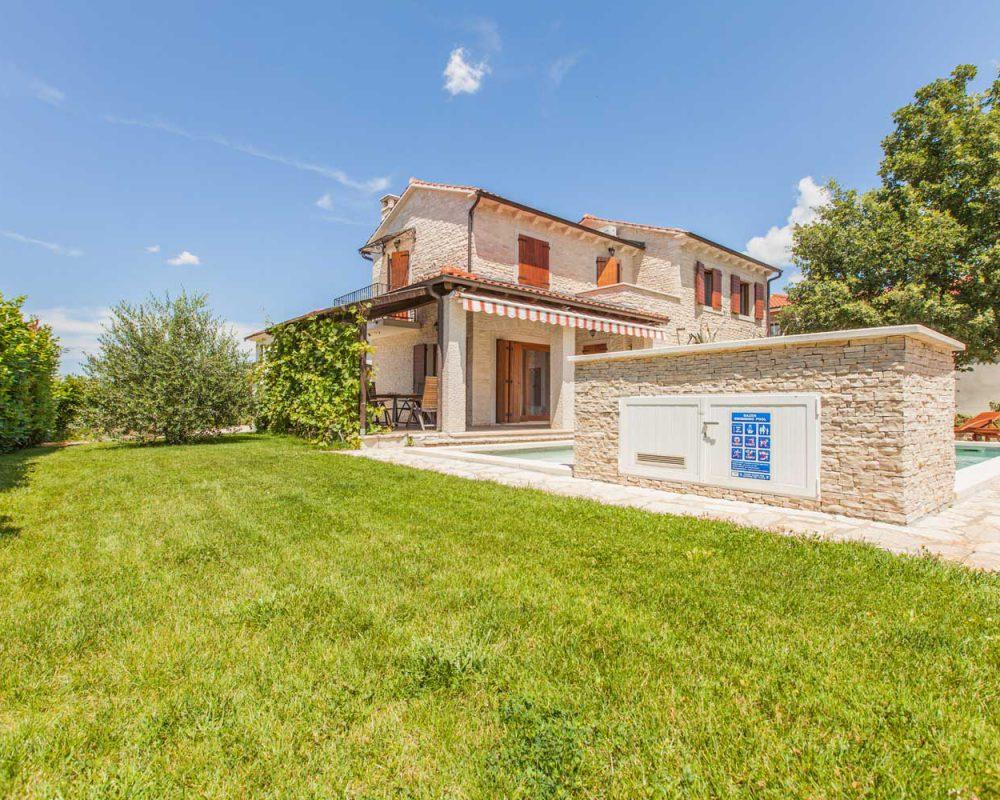 """Der große und grüne Außenbereich des villenartigen Ferienhauses """"Villa Alma"""" mit Swimmingpool und überdachter Terrasse."""