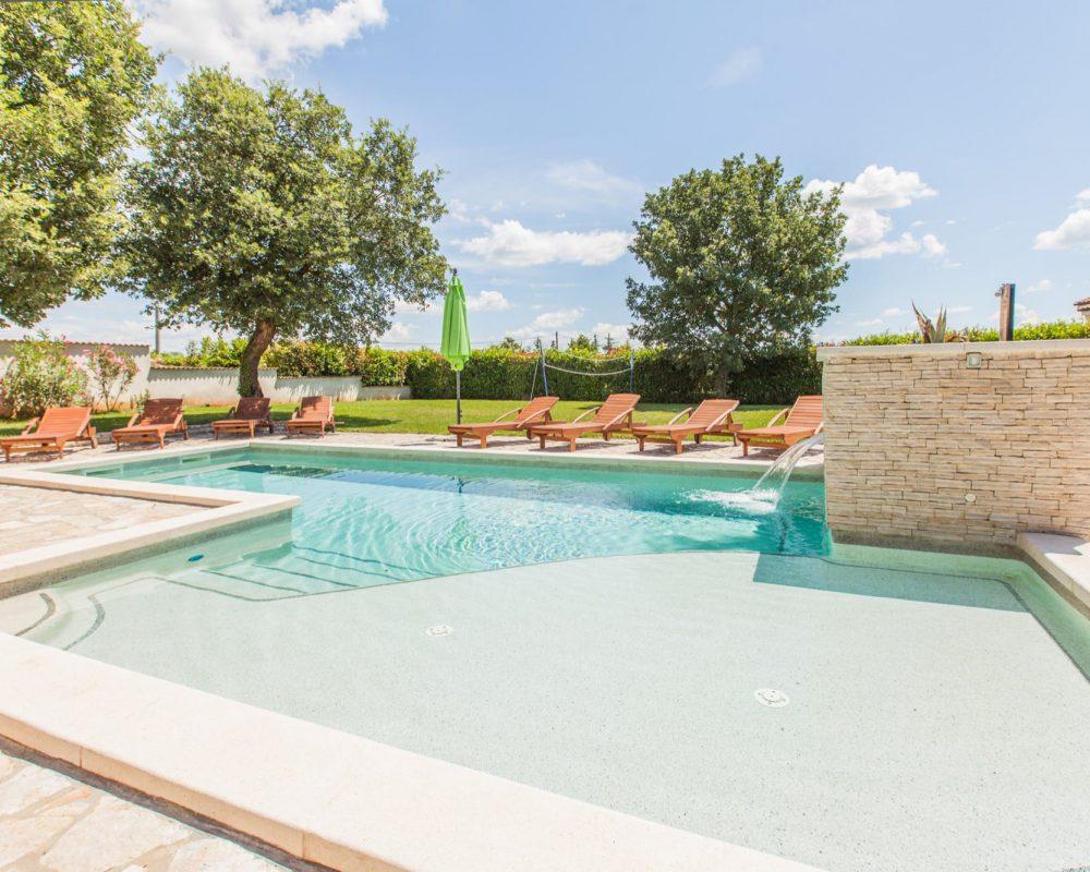 Die Villa Alma, auf der Halbinsel Istrien, hat einen schicken Außenpool mit einem flachen und einem tiefen Bereich. Treppen führen in den Pool.