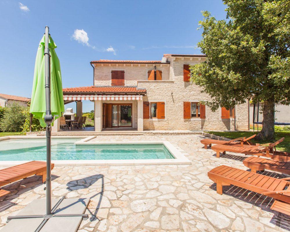 Die Villa verfügt über eine große Steintereasse mit Swimmingpool, Sonnenliegen und einem Sonnenschirm.