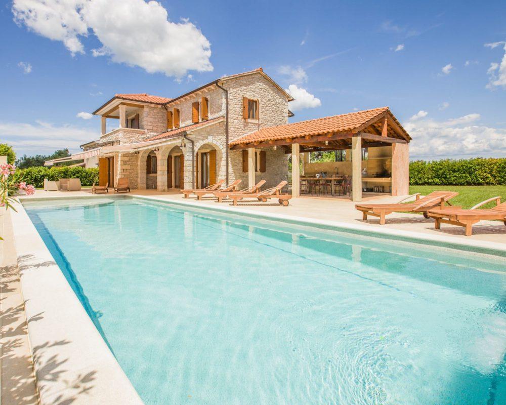Der Blickgeschützte Swimmingpool liegt direkt gegenüber von der Außenküche der Villa Begonia.