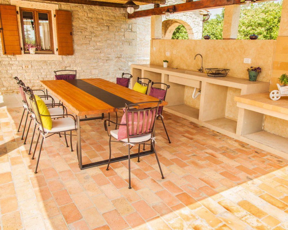Im Außenbereich der Villa befindet sich eine überdachte, rustikale Außenküche. Hier kann gekocht und gegrillt werden.