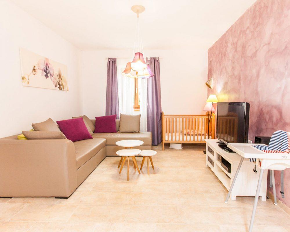 In dem Wohnzimmer befinden sich eine Eckcouch, ein Regal mit einem Flachbild-SAT-TV und ein Gitterbett aus Holz.