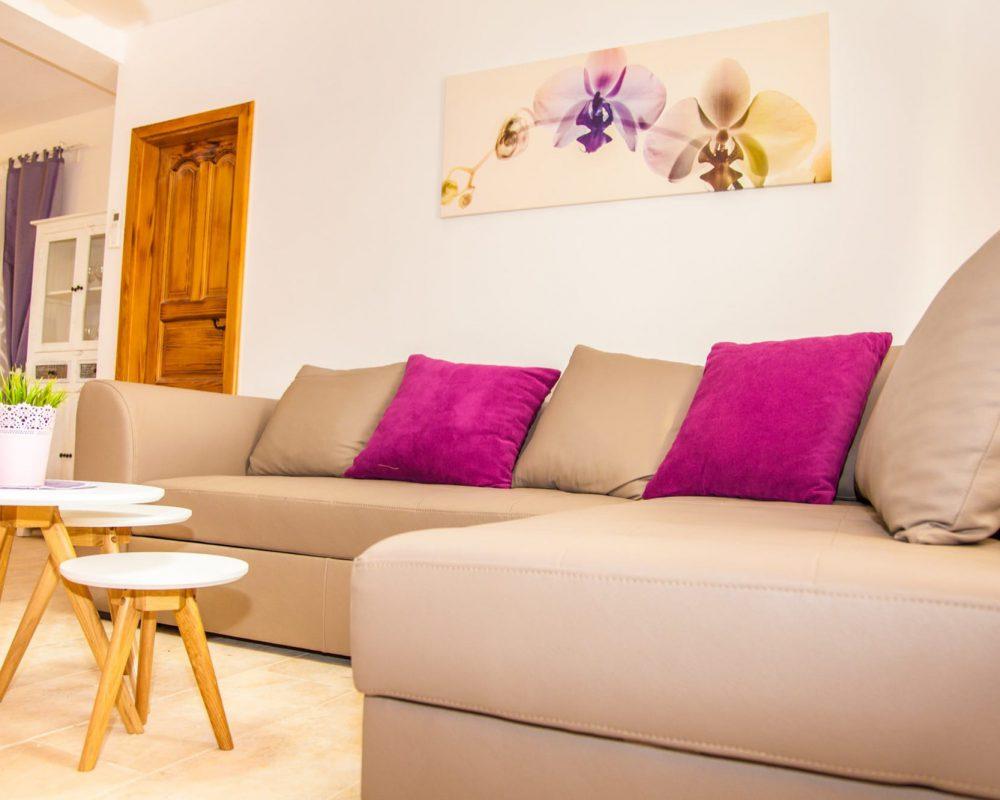 Das Wohnzimmer hat eine bequeme Eckcouch. Vor der Eckcouch stehen drei kleine runde Couchtische.