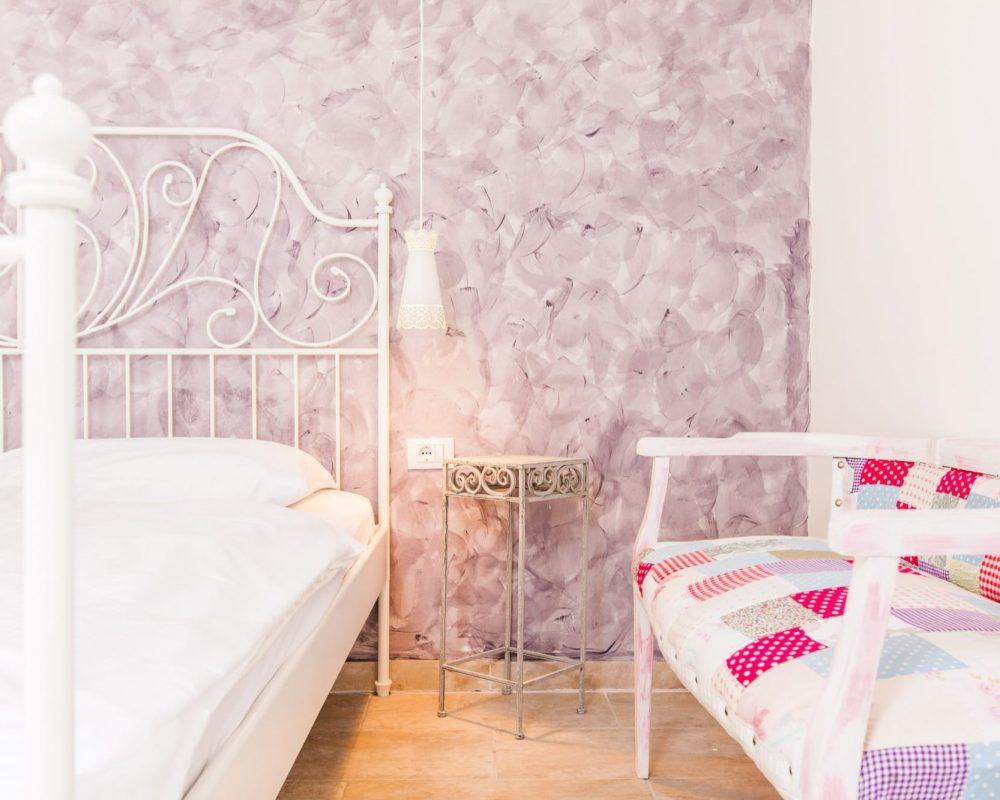 Rechts und Links neben dem Doppelbett ist jeweils ein kleiner verzierter Nachttisch und eine Hängelampe.