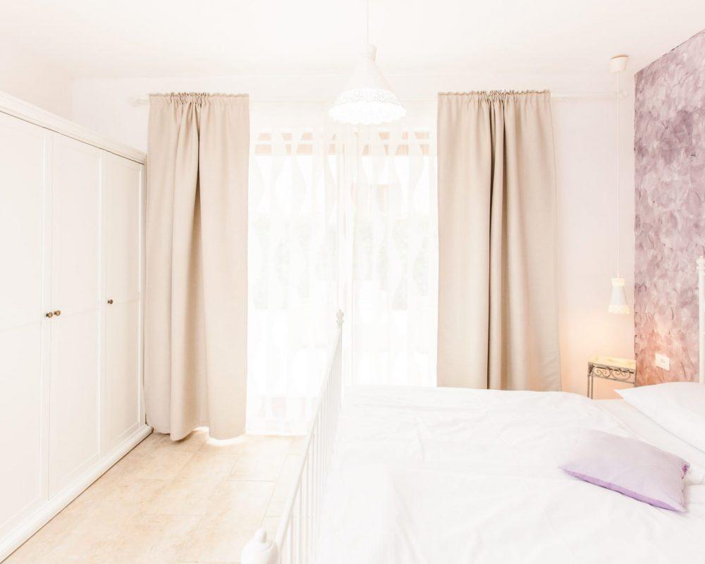 Das romantische Schlafzimmer mit dem Metallbett hat einen direkten Zugang zur großen Terrasse. Gegenüber von dem Doppelbett steht ein großer Kleiderschrank.