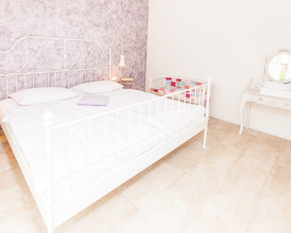 Das romantisch eingeichtete Doppelzimmer, mit dem großen Metallbett, befindet sich im Erdgeschoss. Es hat einen kleinen weißen Tisch mit eine runden Spiegel.