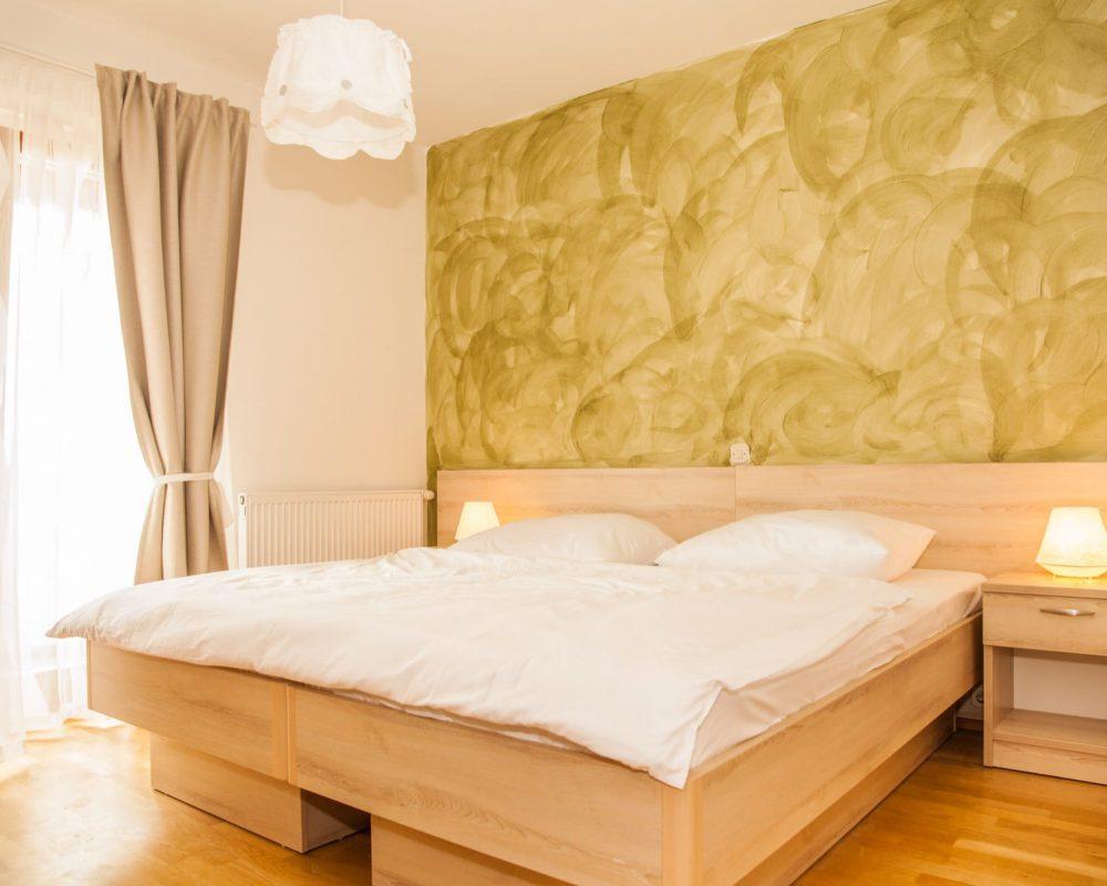 Das große Schlafzimmer beitzt einen kleinen eigenen Balkon und hat eine oliventonfarbene Wand.