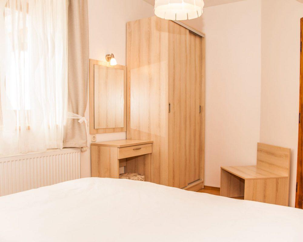 Das Schlafzimmer besitzt einen großen Kleiderschrank, einen Kosmetiktisch mit Spiegel und eine kleine schlichte Holzbank. Ein Fenster erhellt den Raum.