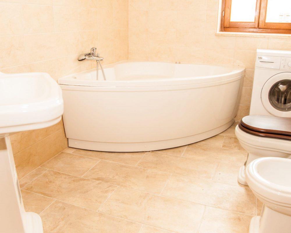 In dem großen Badezimmer befindet sich eine Toilette, eine Waschmaschiene und eine Badewanne.