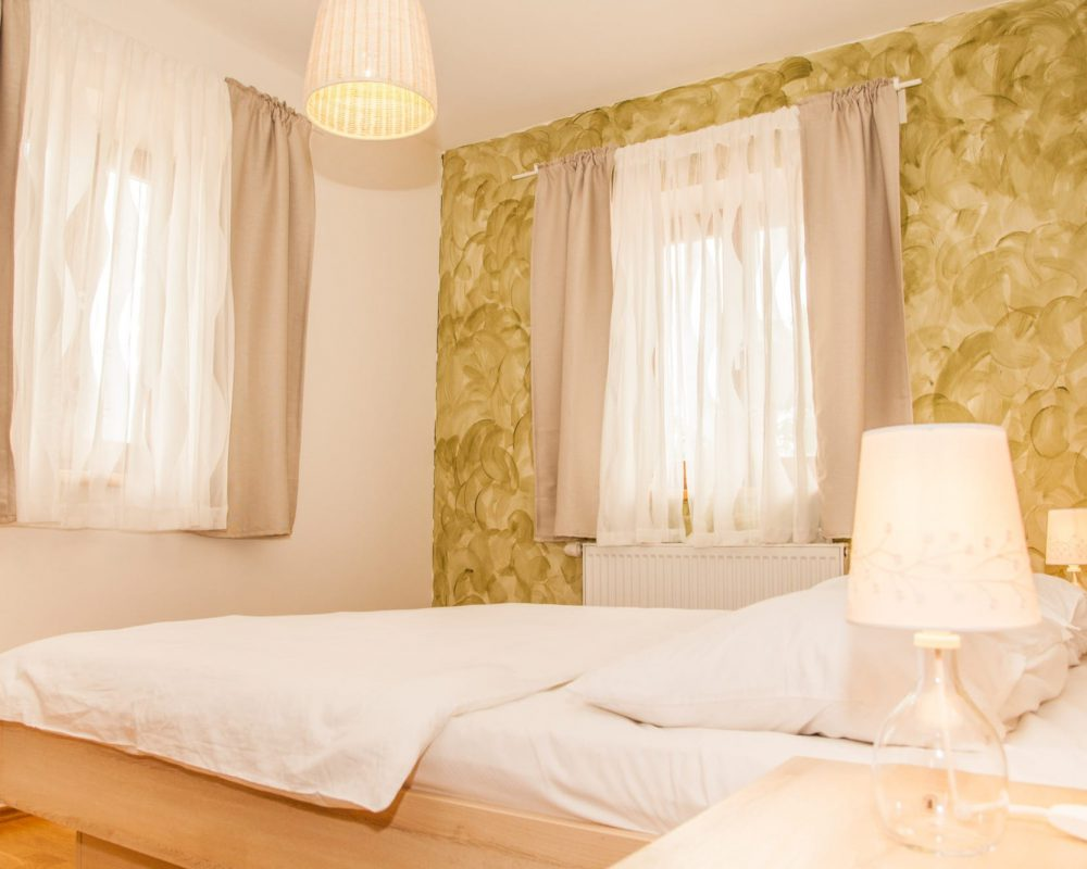 Das große Schlafzimmer mit Doppelbett hat zwei Fenster mit Gardienen. Neben dem Bett stehen zwei Nachttische.