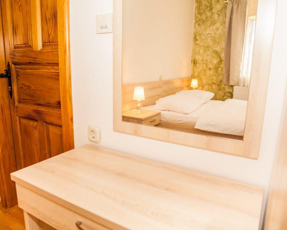 Das große Schlafzimmer hat einen kleinen Tisch mit einer Schublade. Über dem Tisch ist ein rechteckiger Spiegel.