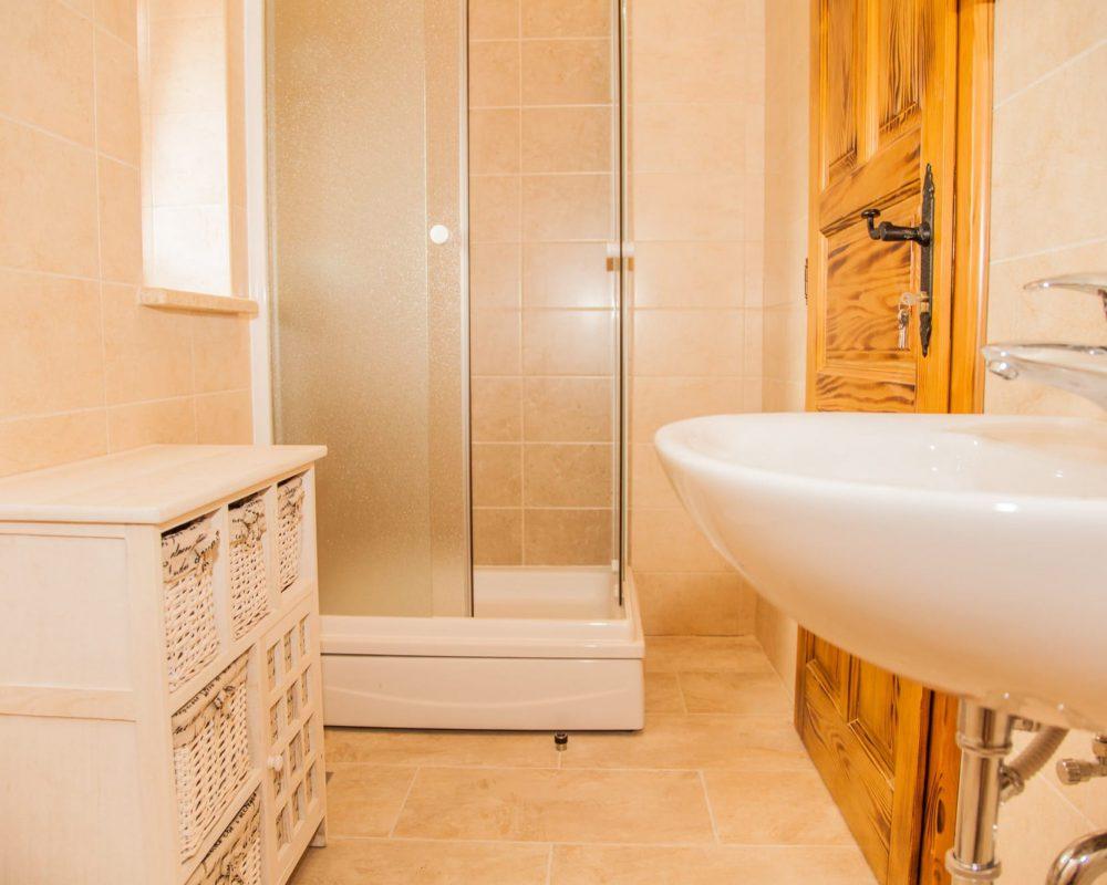 Das kleine badezimmer im Obergeschoss hat eine Dusche und einen kleinen quaratischen Badschrank mit einzelnen Fächern.